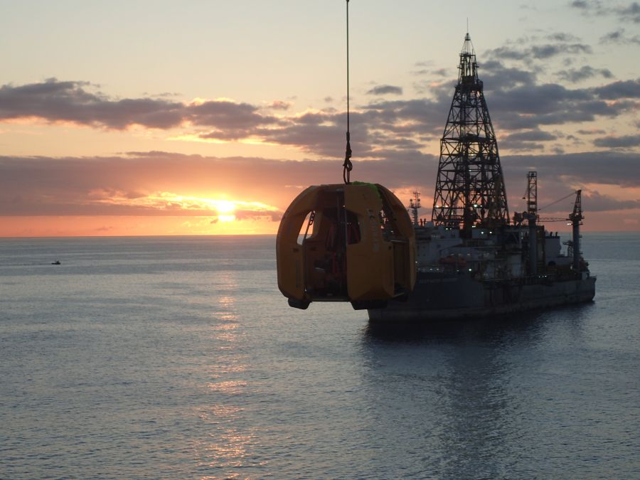 FROG-XT4 by Reflex Marine being transferred via crane by Sten Drilling with the sunset in the background.