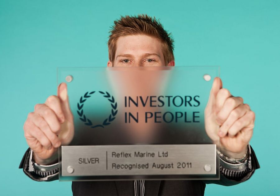 James Strong holding the Silver Award for Investors in People, which Reflex Marine won in 2011 and 2014.