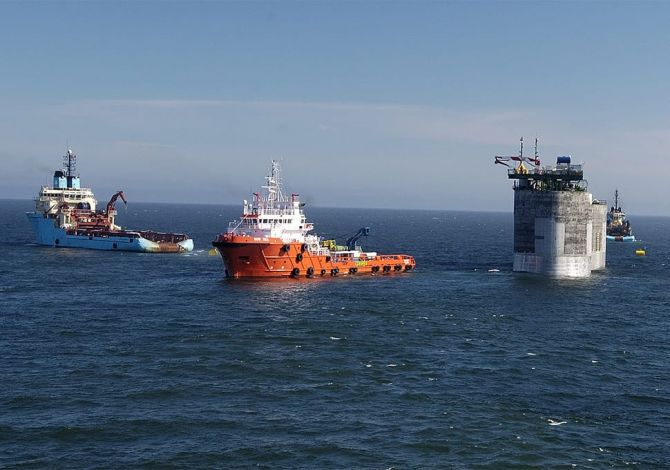 Some ships sail away from an offshore structure after completing a safe crane transfer using a Reflex marine device.