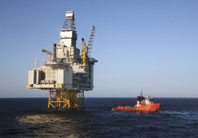 After a safe crew transfer using a Reflex Marine device, a ship sails away from an oil rig.