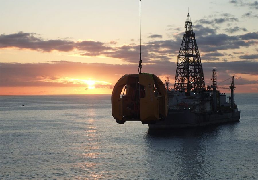 The sun sets behind a Stena Drilling oil rig and the Reflex Marine FROG XT suspended in the air.